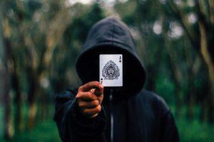 Poker Man in hoodie holding card